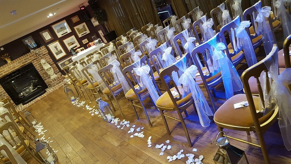 Transformation of ceremony room. Scattered petals, chair bows and floor standing lanterns.