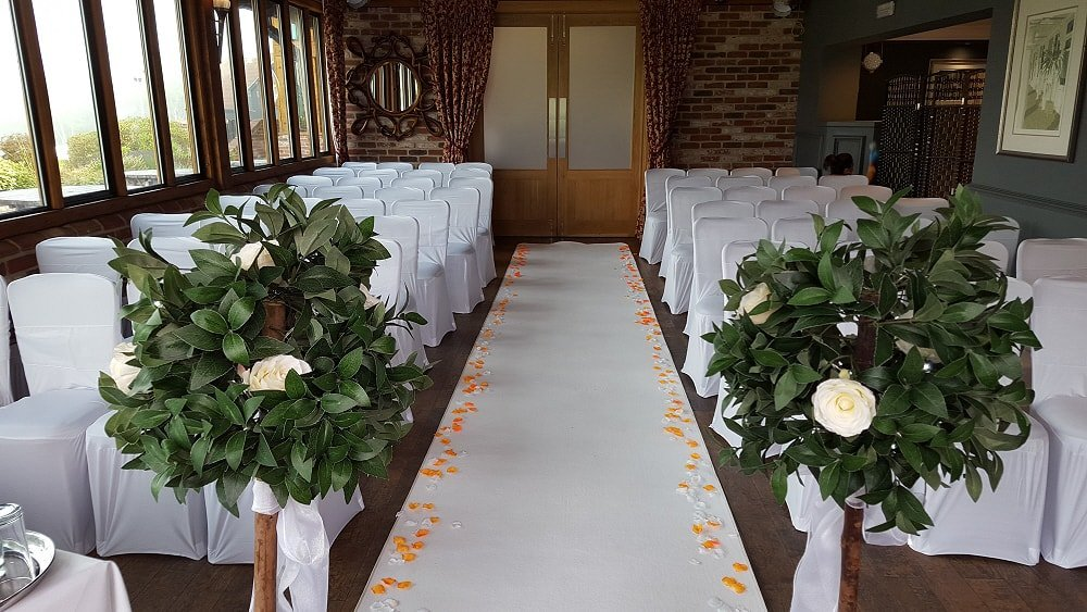 Flower petals scattered on a white aisle carpet, greeted with beautiful bay trees.