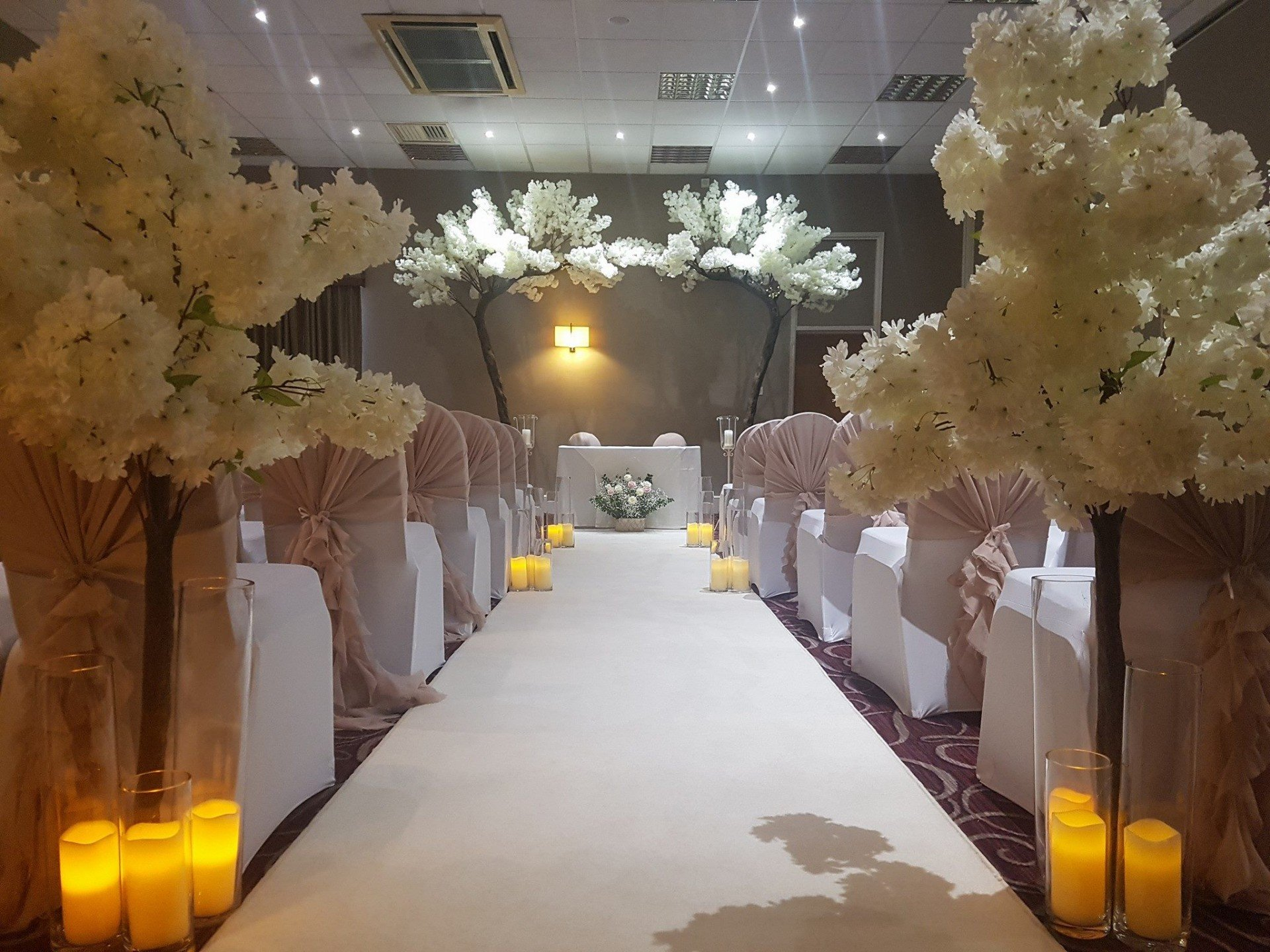 Blossom tress and ceremony arch, partnered with a white candle aisle carpet and beautifully lit walkway.