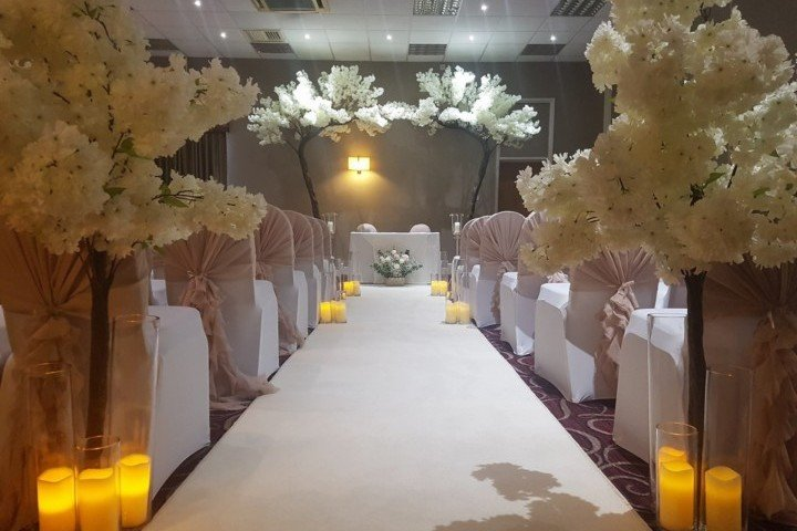 Wedding cermemony venue transformed with floating candles, blossom trees and stylish chair covers.
