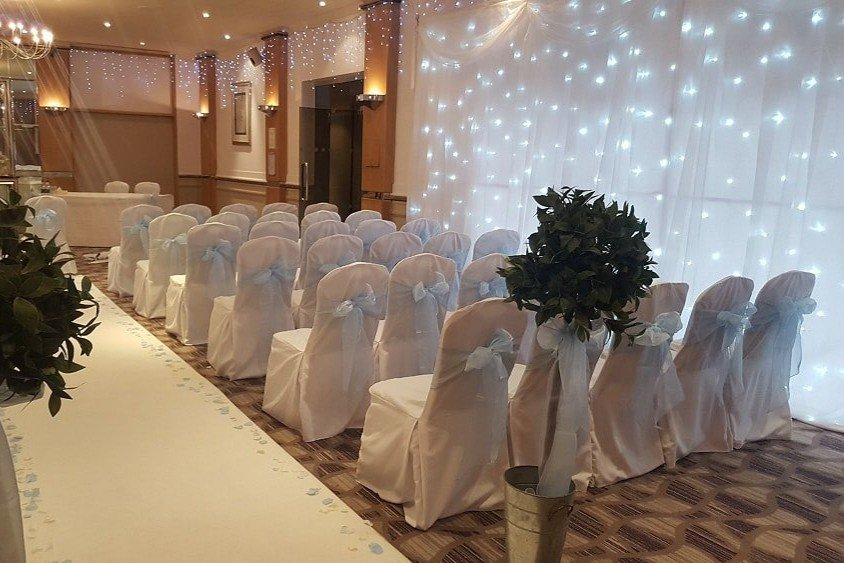 White stretch chair covers with accessory sash tied in a bow. Northampton/Hampshire wedding decor studios.